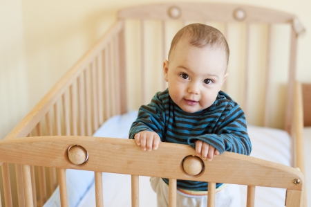 Baby with a cute happy face standing in a cot. photo