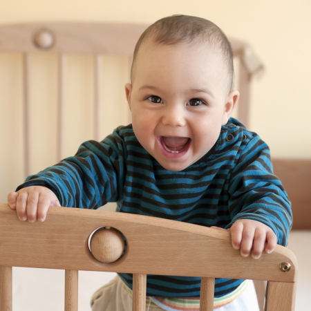 Portrait of  a happy laughing baby standing in a cot. Stock Photo