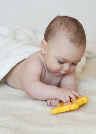 Baby lying on her belly  playing with a plastic toy photo
