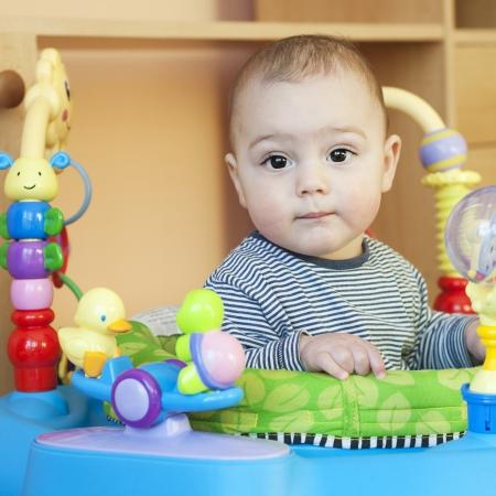 marcheur: Portrait d'un mignon bébé de 6 mois, garçon ou fille, dans une marchette de videur avec des jouets en plastique attachés. Banque d'images