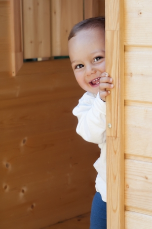 Small smiling happy child playing peeping out of a wooden playhouse or a small garden shed door