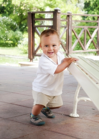 Happy toddler child leaning against a bench in a spring park or a patio garden, trying to get up, learning to walk