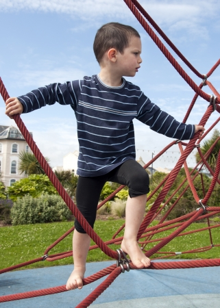 Child playing barefoot at playground on a rope climbing frame equipment  Stock Photo