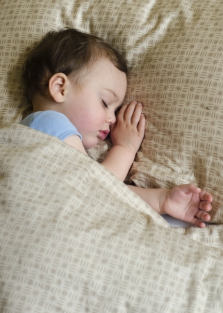 Portrait of toddler child,  boy or gir, sleeping under a blanket in a bed.  photo