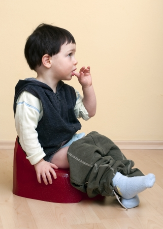 loo: A cute toddler child boy sitting on a red potty.