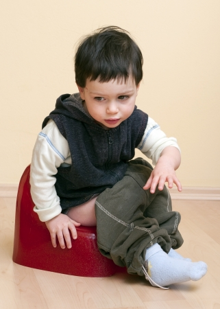 potty: A cute toddler child boy sitting on a red potty.