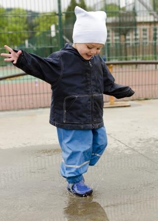 ni�os jugando en el parque: Ni�o feliz ni�o que juega en charco despu�s de la lluvia.