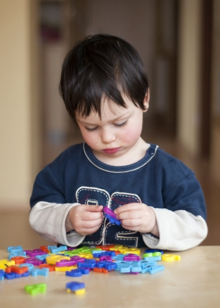 Portrait of a small child, boy or girl, playing with colorful plastic letters. Stock Photo