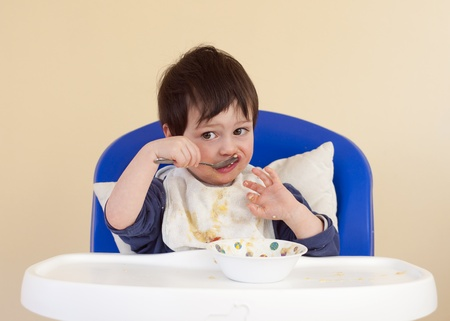 messy kitchen: Child, baby or toddler sitting in a high chair eating with spoon from a bowl.
