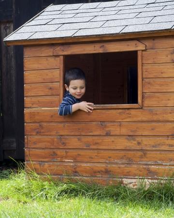 Kind jongen in een raam van een houten tuinhuisje of speelhuis. Stockfoto