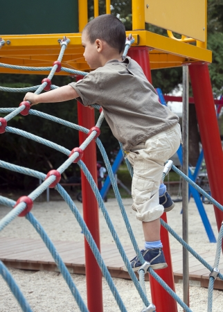strenght: Child playing in playground on a modern rope climibing equipment.  Stock Photo