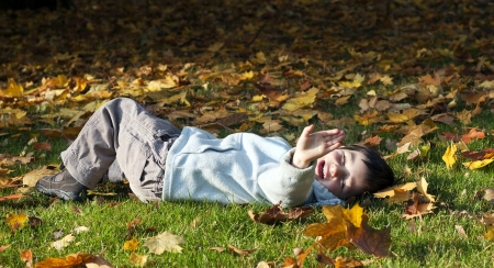 oudoors: Child lying on grass  in a park playing with yellow autumn or fall leaves