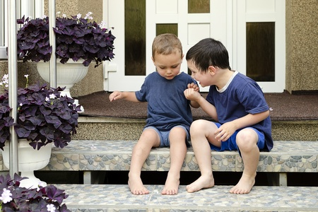 Children, two small boys brothers, sitting on a stairs in front of a house.  photo