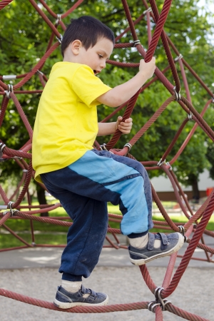 Child playing in playground on a modern rope climibing equipment. photo