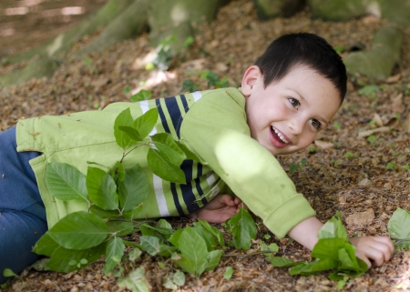 Happy child playing undrer a tree in park or a forest. photo