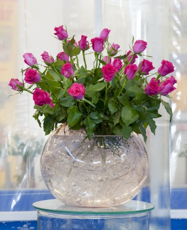 glass vase: Red, pink and yellow rose bouquets arranged in a round glass vases