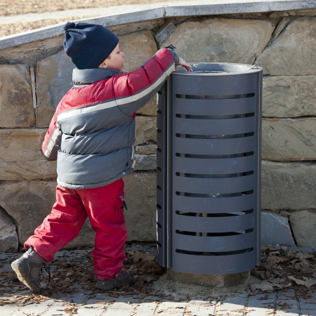 putting on: Small child putting a waste or litter in a street rubbish can or bin. Stock Photo
