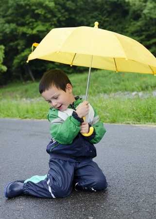 Child with yellow umbrella in the rain.  photo