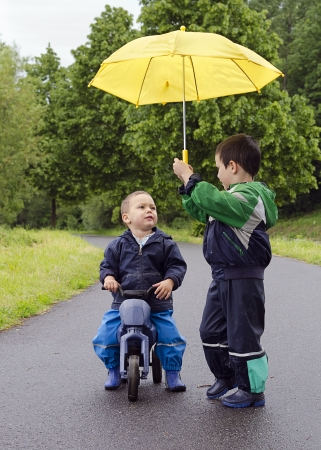 Children friends with yellow umbrella and toy bike in the rain.