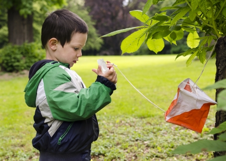 portrait orientation: Child at at control point at orienteering course.