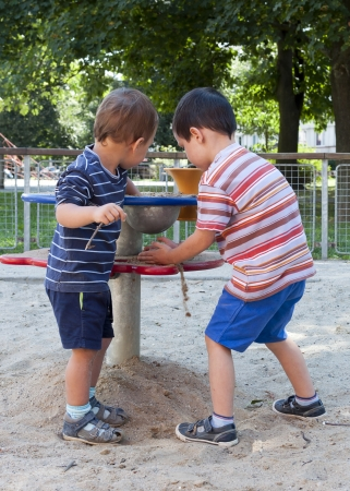 sandpit: Children playing with sand at playground on a play table equipment
