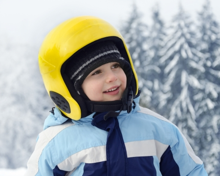 Portrait of a cute happy child skier, boy or girl, with yellow skiing helmet in a winter ski resort  photo