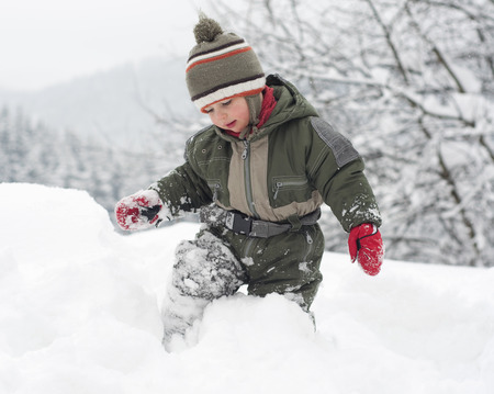 Child toddler standing and walking through a deep fresh snow in winter   photo