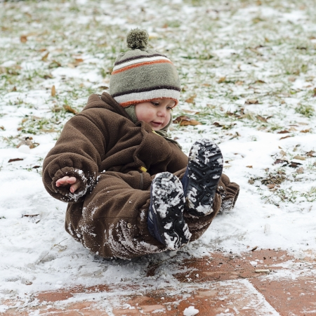 snow falling: Child toddler falling on icy slippery pavement or sidewalk in winter.  Stock Photo