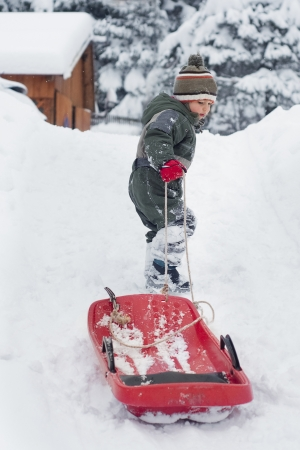 Child boy or girl pulling a sledge in fresh snow in winter photo