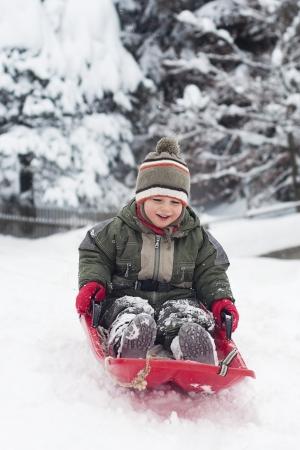 sledging: Felice smilling bambino, ragazzo o ragazza, slitta nella neve fresca in inverno.