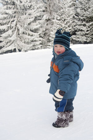 Portrait of a toddler child, boy or girl, i playing in a fresh snow. photo