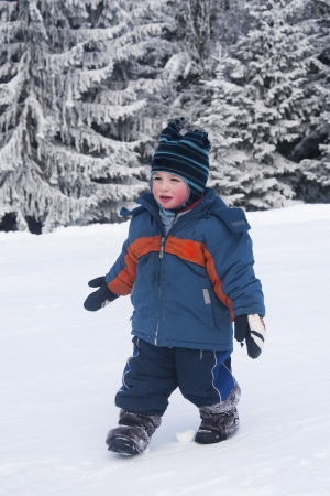 Portrait of a toddler child, boy or girl,  playing in a fresh snow. photo