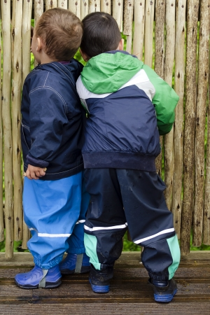 Two children, boys, looking through the wooden fence or wall, back view.  photo