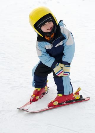 Child learning to ski in winter skiing resort practicing the correct moves.  Stock Photo