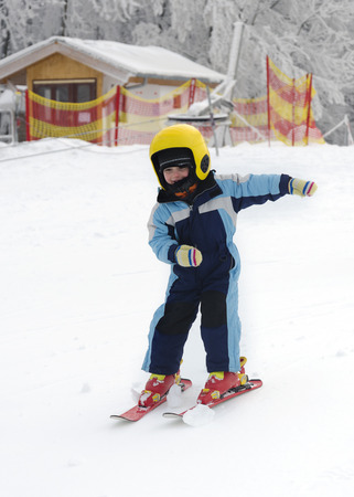 Child learning to ski in winter skiing resort.