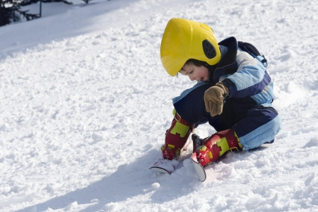 Child skier sitting on snow after falling down whilst learning skiing.