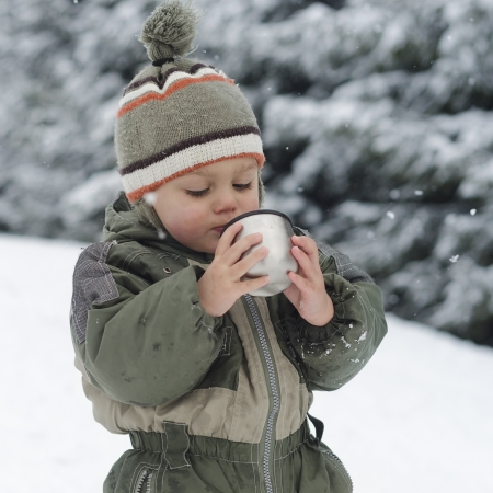 Child toddler in winter snow drinking a hot drink.