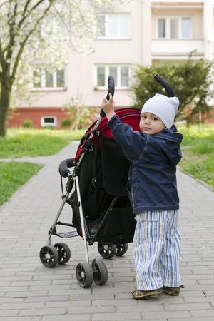niño empujando: Niño pequeño niño, muchacho o muchacha, empujando un cochecito en un sendero peatonal