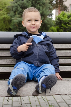 Child boy sitting on a bench eating ice cream lolly.  photo