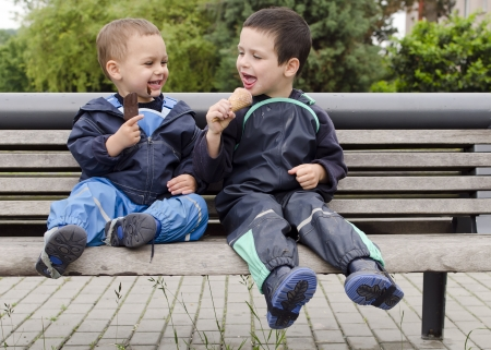 Two happy children, boys, friends or brothers, sitting on a bench eating ice cream