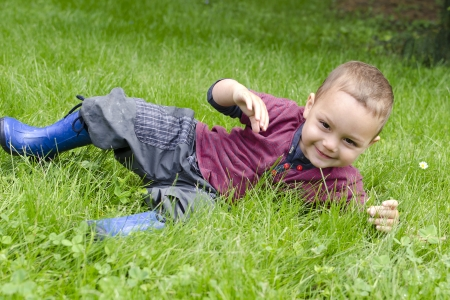 rolling: Happy toddler child playing and rolling in grass in garden or meadow