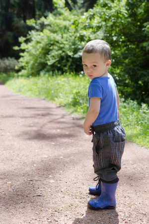 lost child: Child toddler standing on a path in park with shy or lost expression  Stock Photo