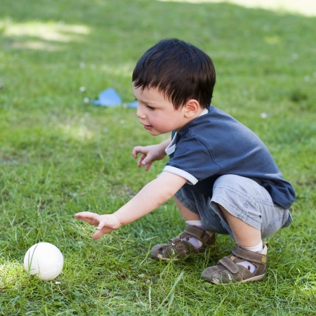 toddler playing: A child boy playing with a small  ball on a grass in the garden