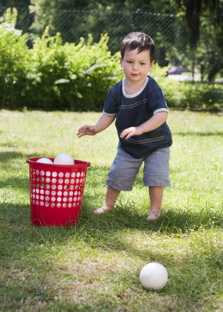 A child boy playing with a small  balls on a grass in the garden