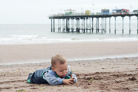 Toddler child in waterproof clothes playing with sand on beach; Teignmouth, Devon, England, UK. Фото со стока