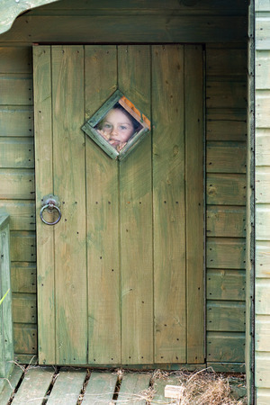 looking through window: Child boy  playing in a wooden garden shed, looking through the small window in a door .