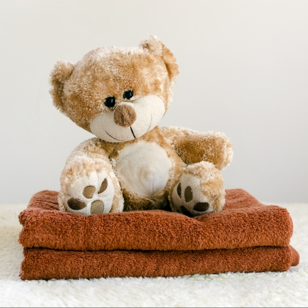 wash cloth: Teddy bear soft toy on a freshly washed brown towels
