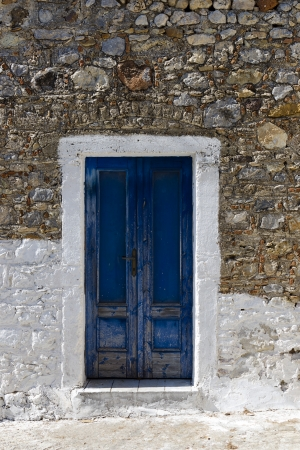 Blue wooden door in old stone mediterranean building, Greece.  photo