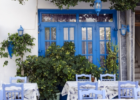 Street restaurant or  in with table and chairs in front of white house with blue window, Kos, Greece.