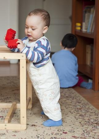 Twee kinderen, kleine peuter of een baby kind en zijn oldrer broer, spelen thuis met bouwstenen. Stockfoto - 24858369